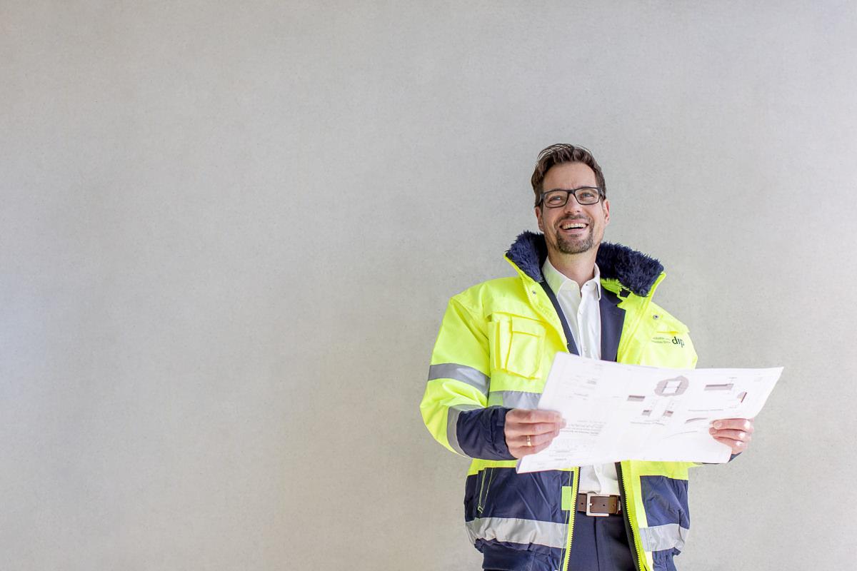 Portraitfoto eines Mitarbeiters des Bauunternehmens dip, der einen Bauplan in der Hand hält