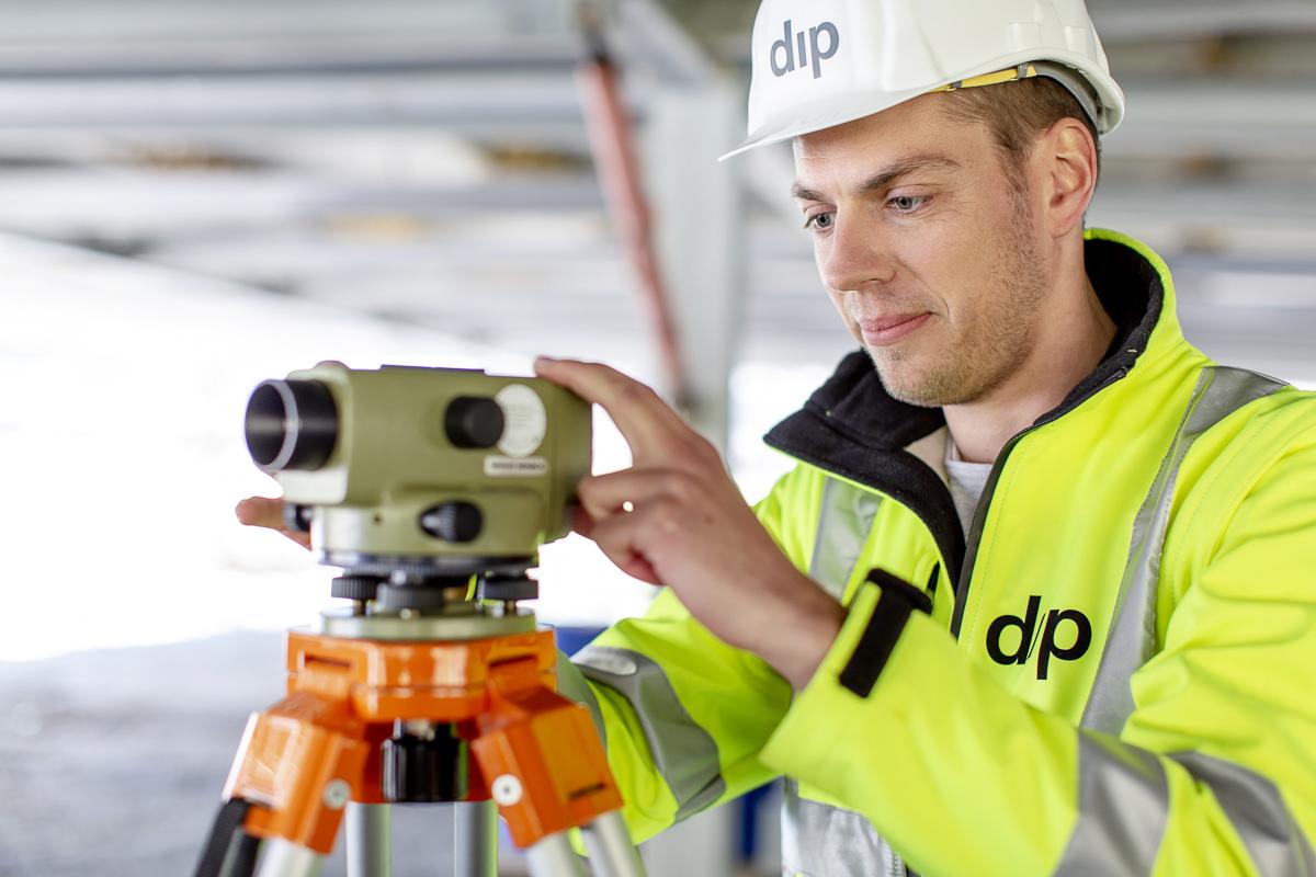Industriefoto von einem dip Mitarbeiter bei der Vermessung auf einer Baustelle