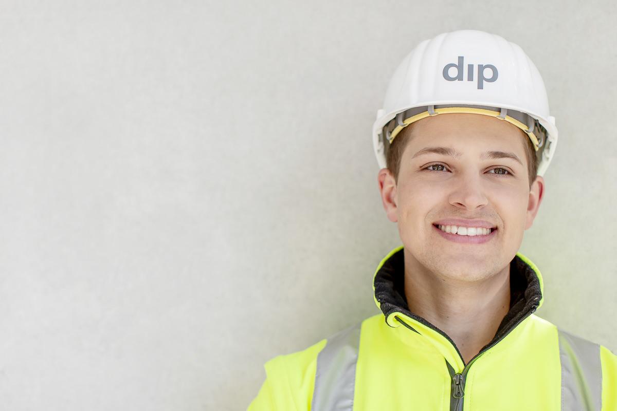 sympathisches Portraitfoto eines Mitarbeiters des Bauunternehmens dip