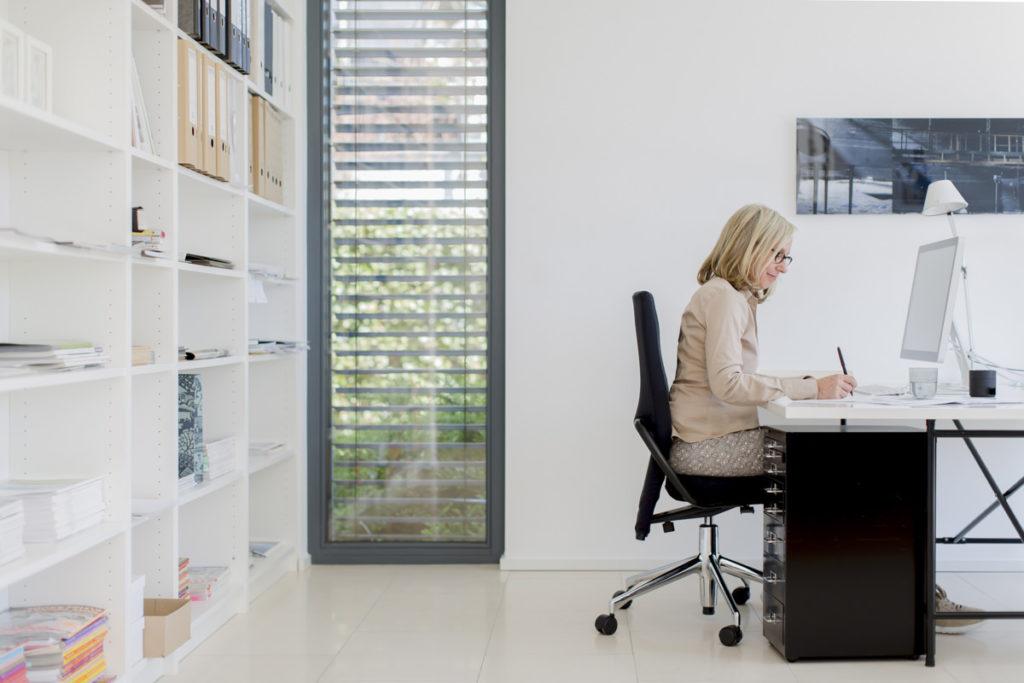 Portraitfoto von Innenarchitektin Judith Heisterkamp bei der Arbeit in ihrem Büro in Neuss