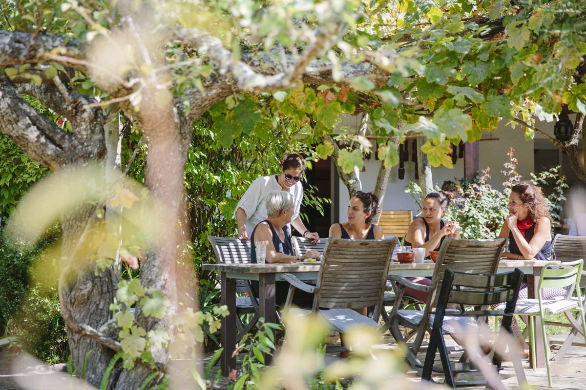 Teilnehmer eines Yoga Retreat in Portugal sitzen gemeinsam am Tisch