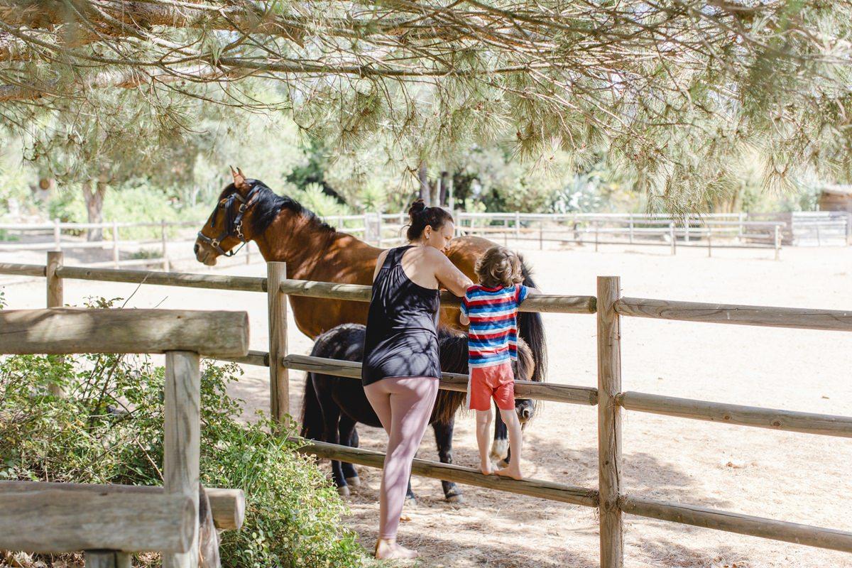 Foto von Mutter und Kind mit einem Pferd bei einem Yoga Retreat in Portugal