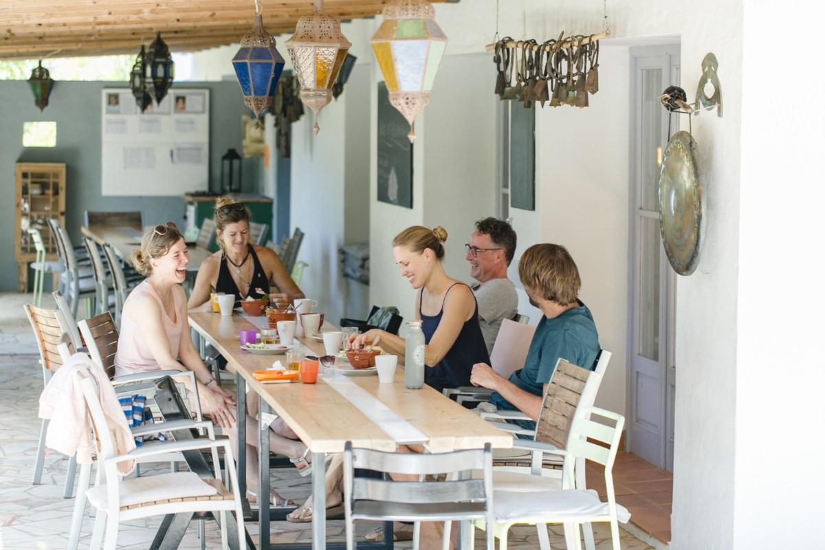 Teilnehmer eines Yoga Retreat in Portugal sitzen gemeinsam beim Frühstück