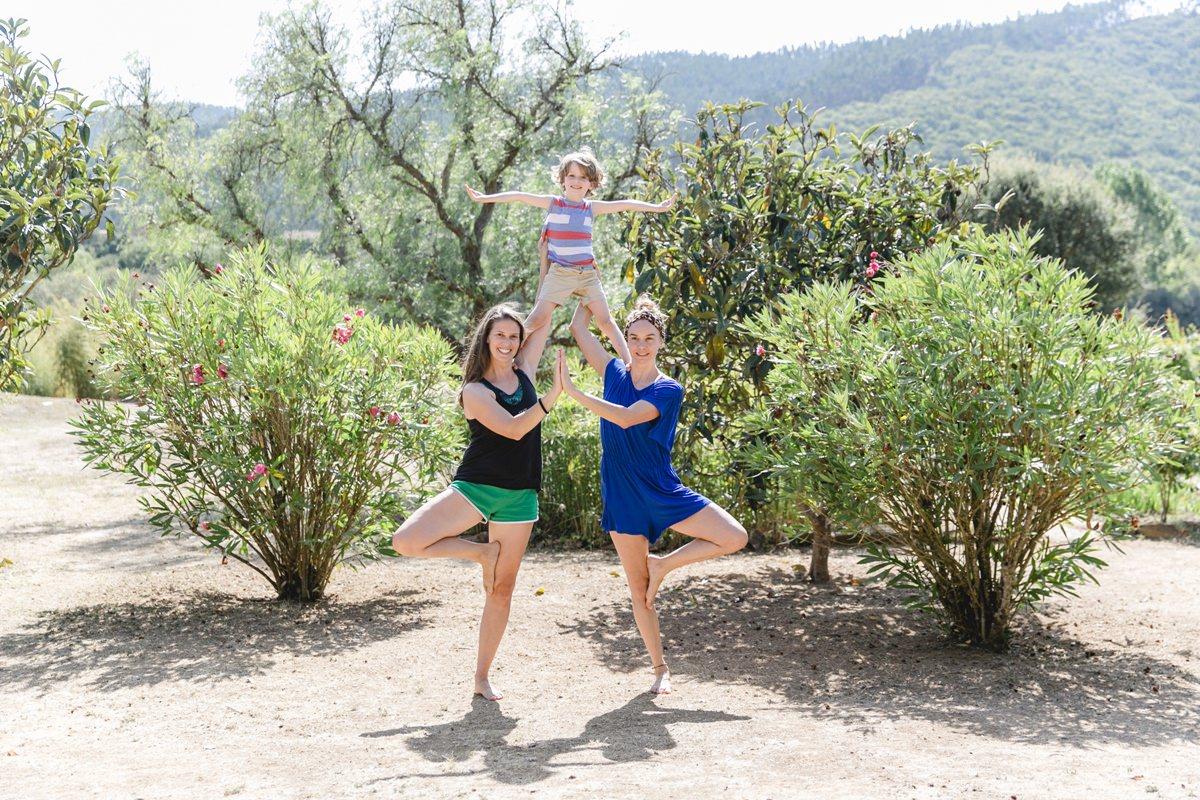 Foto von 2 Frauen und einem Kind, die gemeinsam eine Yoga Übung bei einem Yoga Retreat in Portugal machen