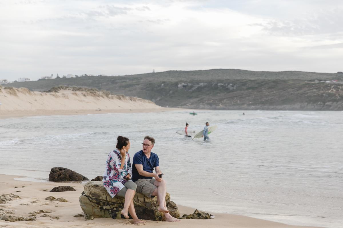 Foto von entspannten Teilnehmern eines Yoga Retreat in Portugal am Strand