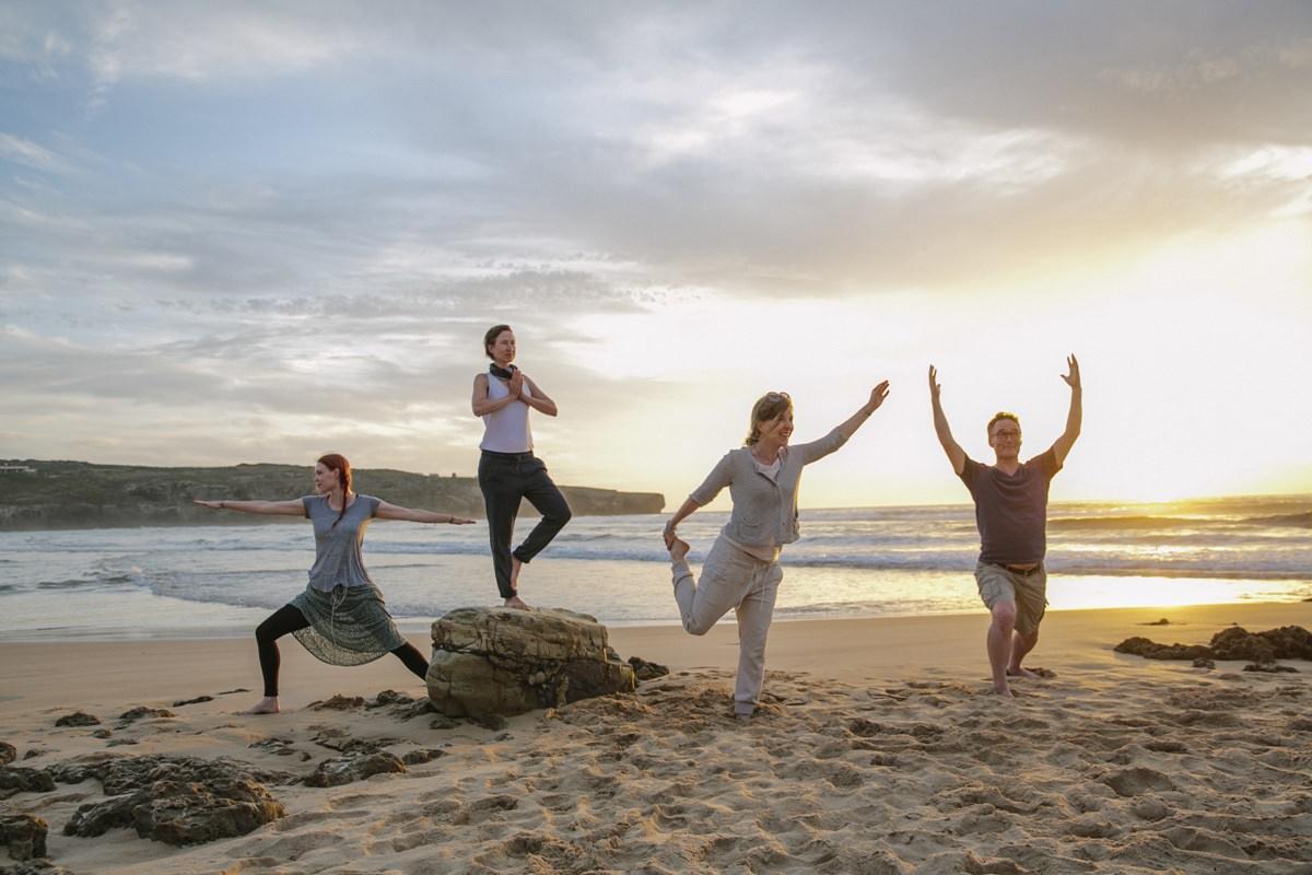 Foto von Teilnehmern einer Yoga Klasse am Strand eines Yoga Retreat in Portugal