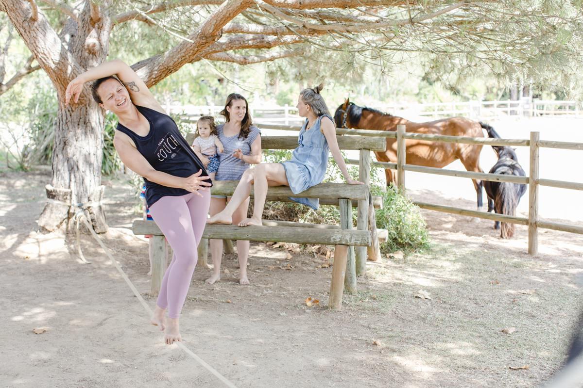 Foto von Teilnehmern eines Yoga Retreat in Portugal, die vor einer Pferdekoppel sitzen