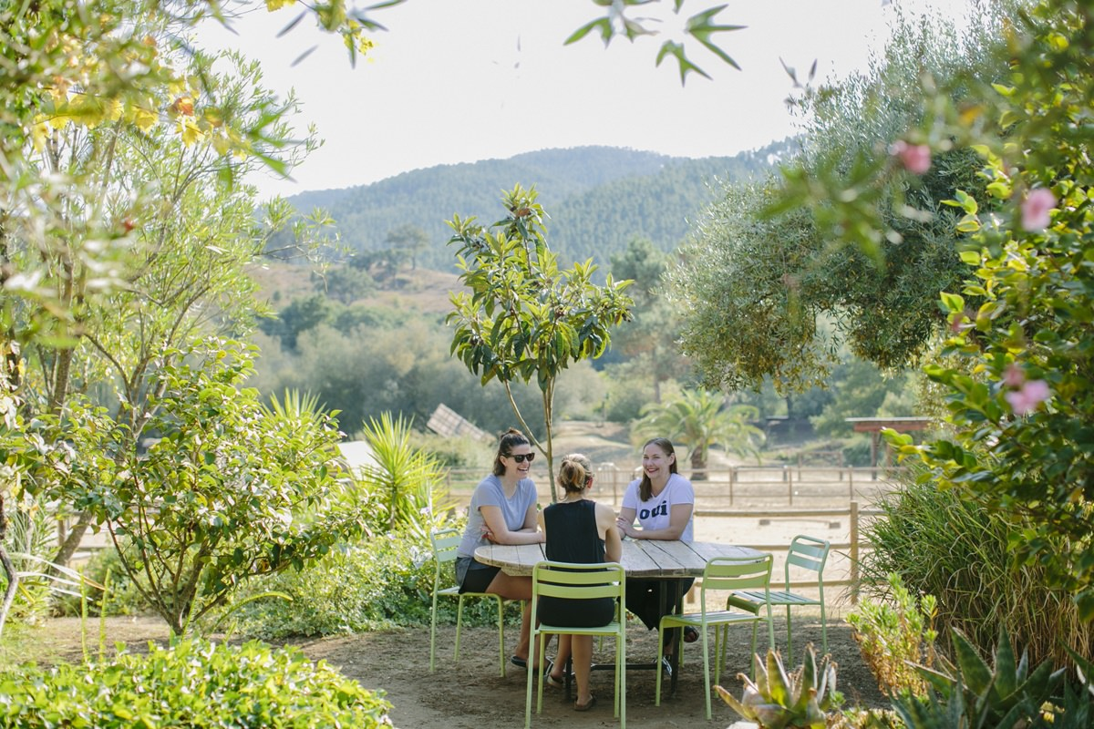 Foto von Yoga Urlaubern, die gemeinsam am Tisch sitzen