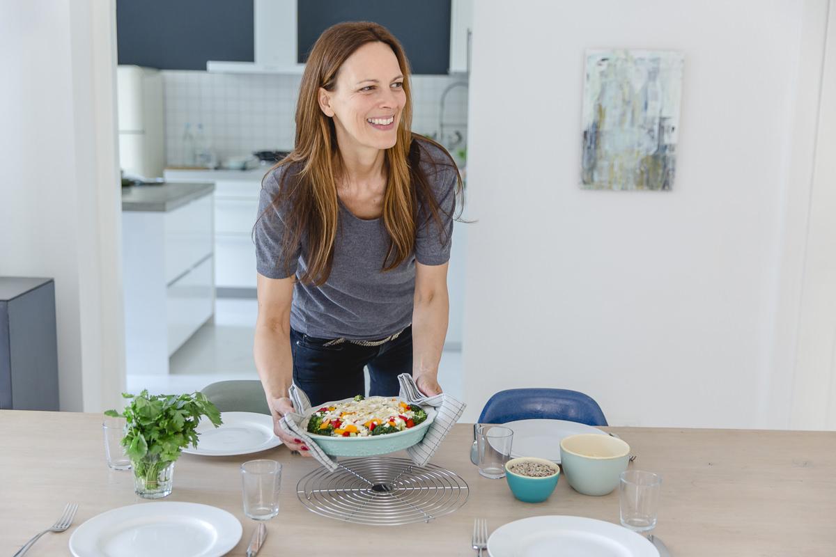 Portraitfoto von Foodbloggerin Sandra Ludes, die ein frisch gekochtes Gericht serviert