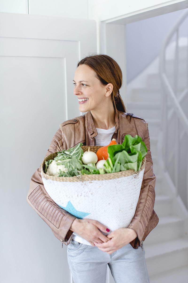 Portraitfoto von Foodbloggerin Sandra Ludes mit einer großen Einkaufstasche voller Gemüse