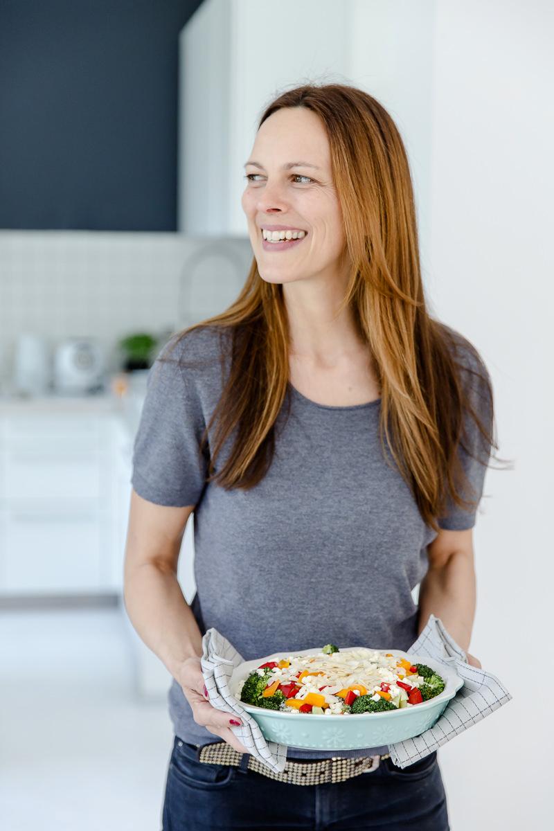 Portraitfoto von Kochbuchautorin Sandra Ludes mit einem selbstgekochten Gericht