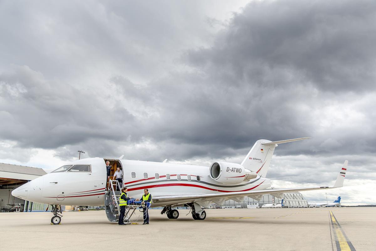 Die Crew eines Ambulanzflugzeugs von Air Alliance lädt einen Patienten aus