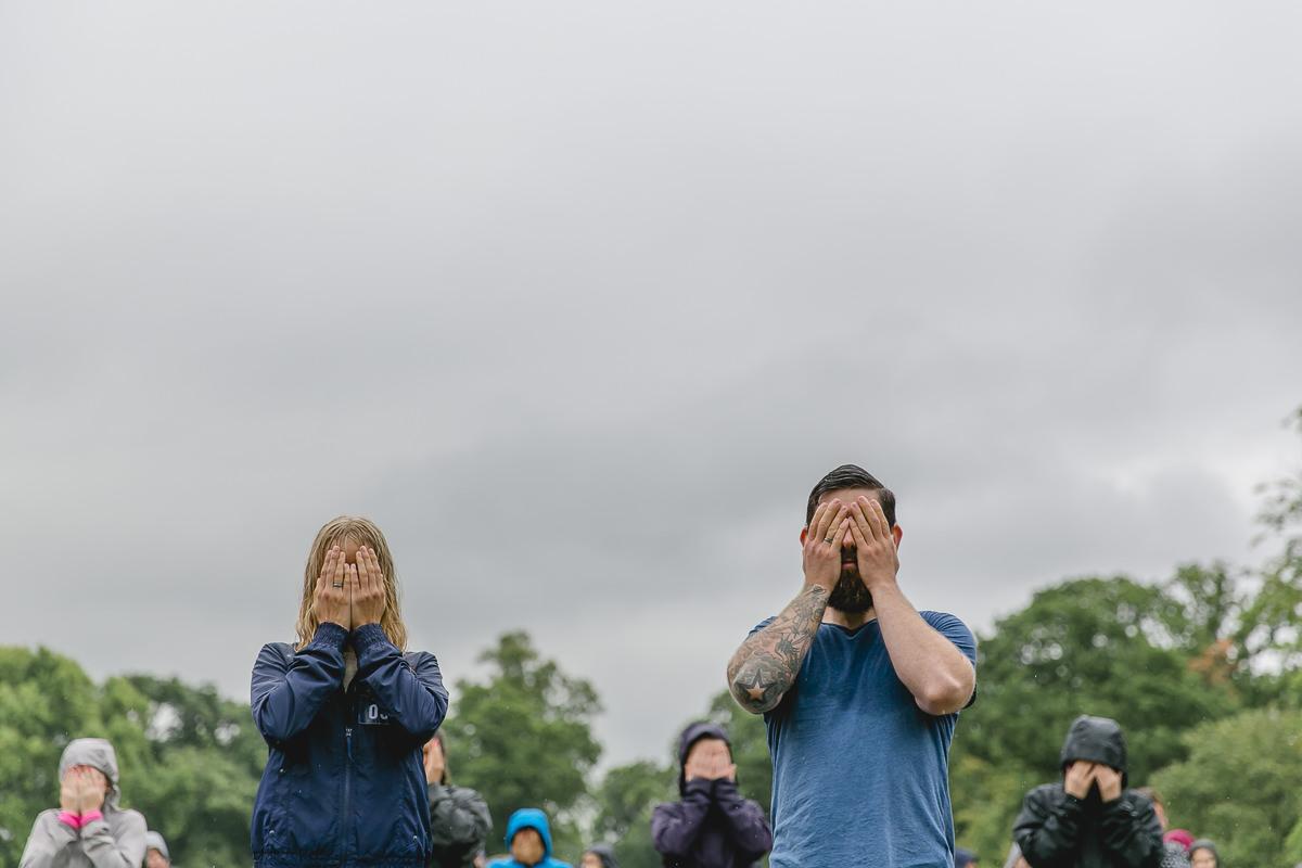 Teilnehmer des Wanderlust Yoga Festivals halten sich die Augen zu