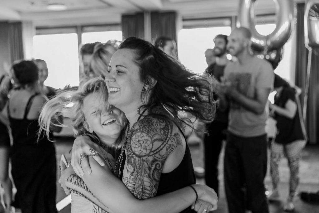 glückliche Teilnhmer der Yoga Conference liegen sich in den Armen