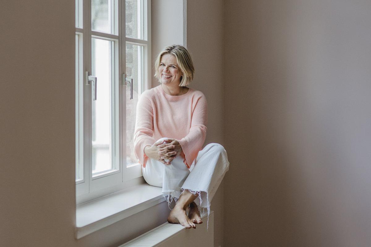 Portraitfoto von Yogatherapeutin Daniela Stilke, die lächelnd an einem Fenster sitzt