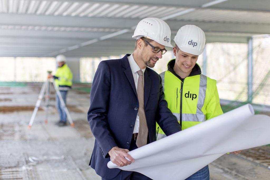 2 Mitarbeiter von dip studieren einen Bauplan auf einer Baustelle
