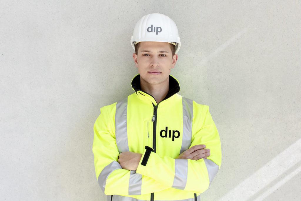 Portrait eines jungen dip Mitarbeiters mit gelber dip Jacke und weißem dip Schutzhelm