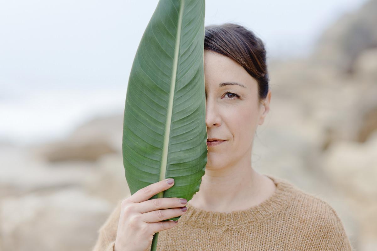 Portraitfoto von Yogalehrerin Christine Mack, die sich ein Blatt halb vor ihr Gesicht hält