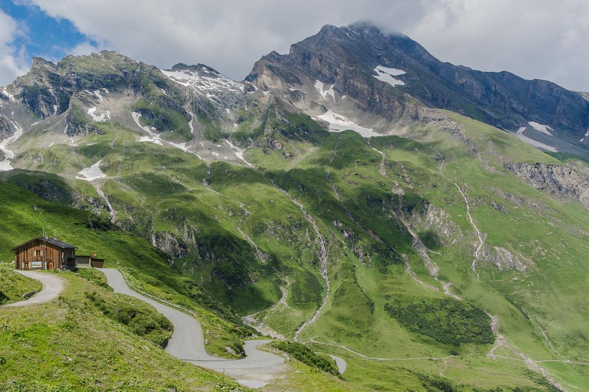 Foto von Bergen mit Wiese und Holzhütte