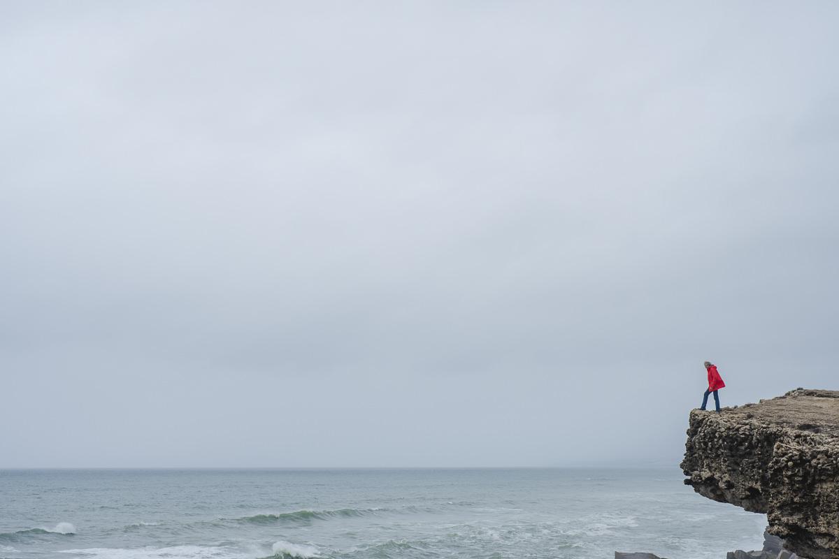 ein Mann auf einem Felsen an der Küste Portugals