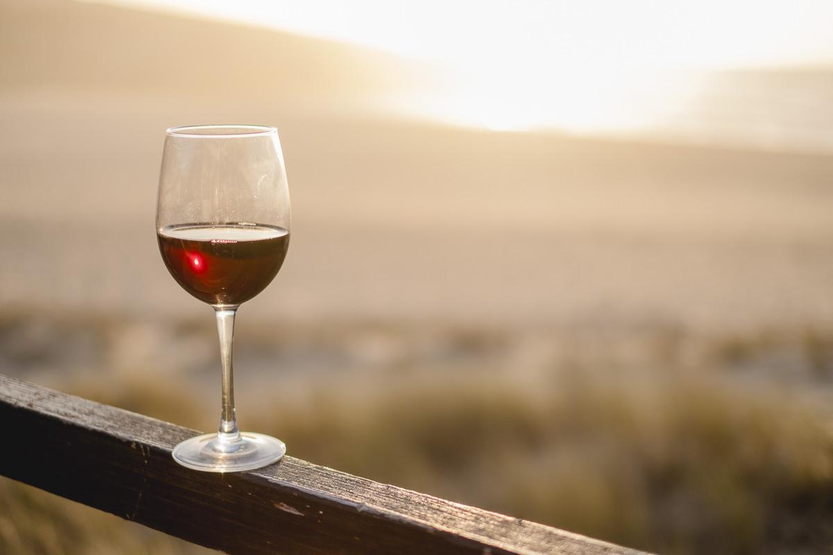 ein Rotweinglas vor dem Sonnenuntergang Portugals