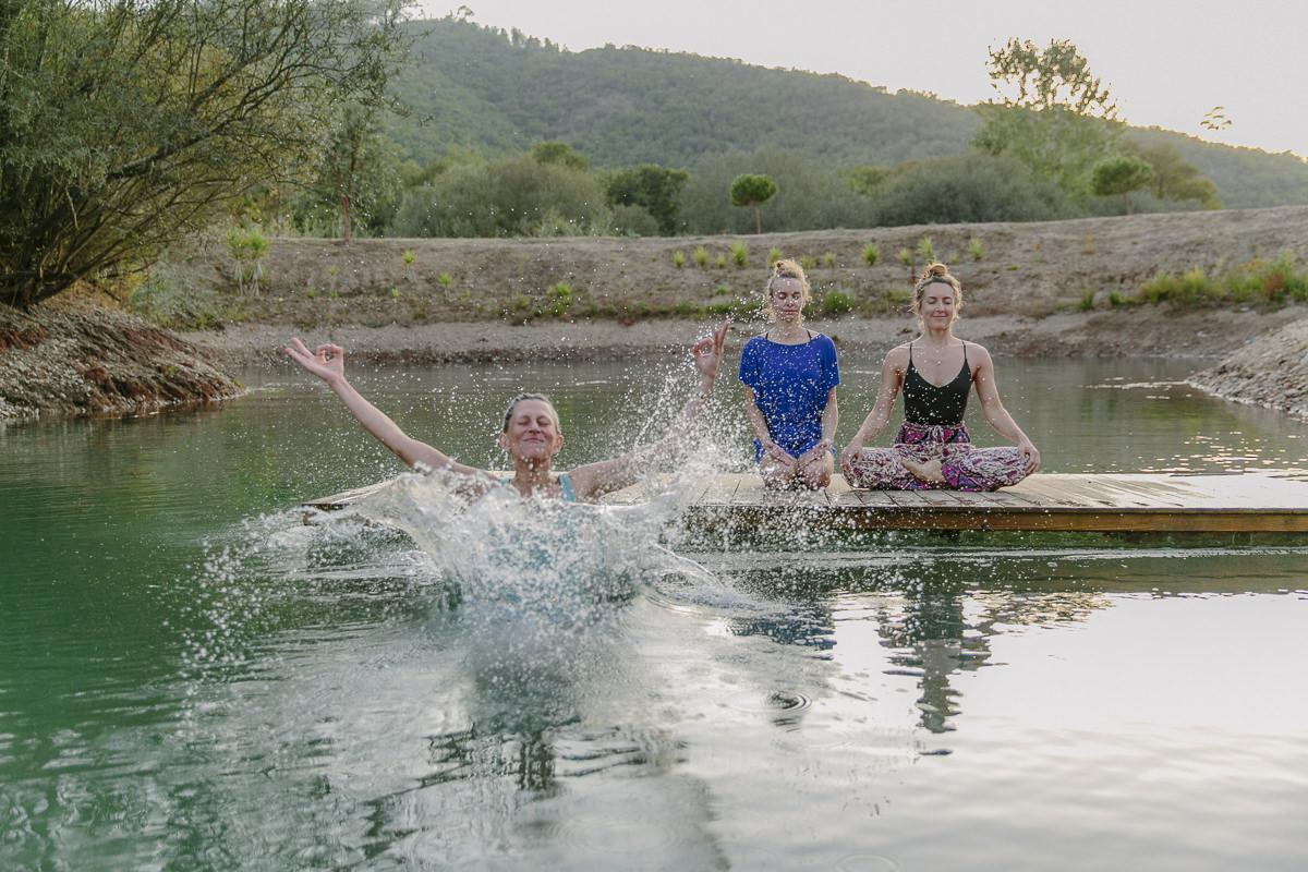 Teilnehmer eines Yoga Retreats bei einer Übung am Wasser