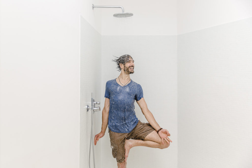 Ein Yogalehrer macht ein Yoga Asana unter der Dusche