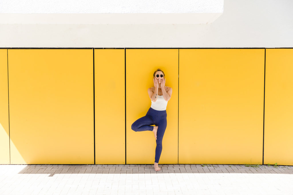 Yogalehrerin bei einem Outdoor Yoga Asana vor einer gelben Wand
