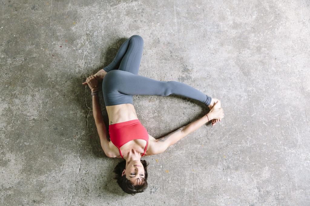 Wanda Badwal liegt auf dem Boden und zeigt ein Yoga Asana