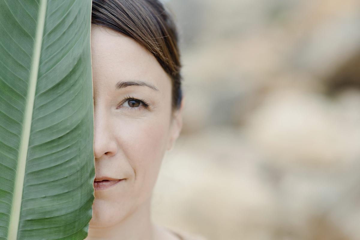 Business Portrait von Yogalehrerin Christine Mack mit einem großen Blatt | Foto: Hanna Witte