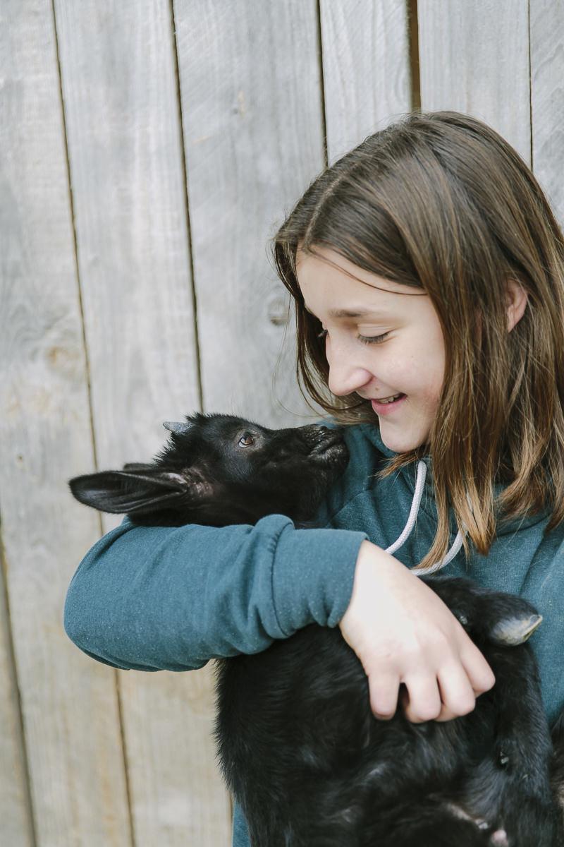 auf dem Ottonenhof hält ein Mädchen eine kleine schwarze Ziege im Arm | Foto: Hanna Witte