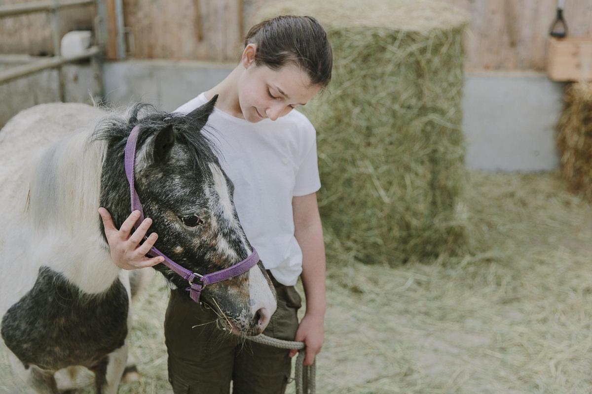 im Reitstall des Ottonenhofs streichelt ein Mädchen ein Pony | Foto: Hanna Witte