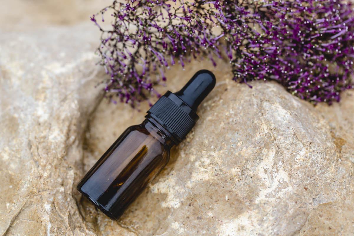Imagefoto von einem Fläschen mit Ätherischem Öl, das auf einem Stein liegt | Foto: Hanna Witte