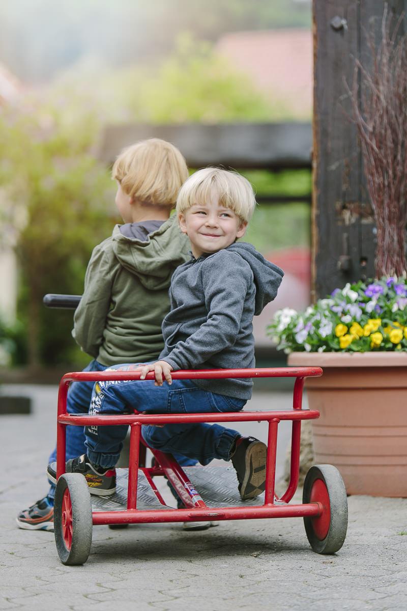 Kinder fahren auf dem Gelände des Familienhotels Ottonenhof mit einem Tretauto | Foto: Hanna Witte