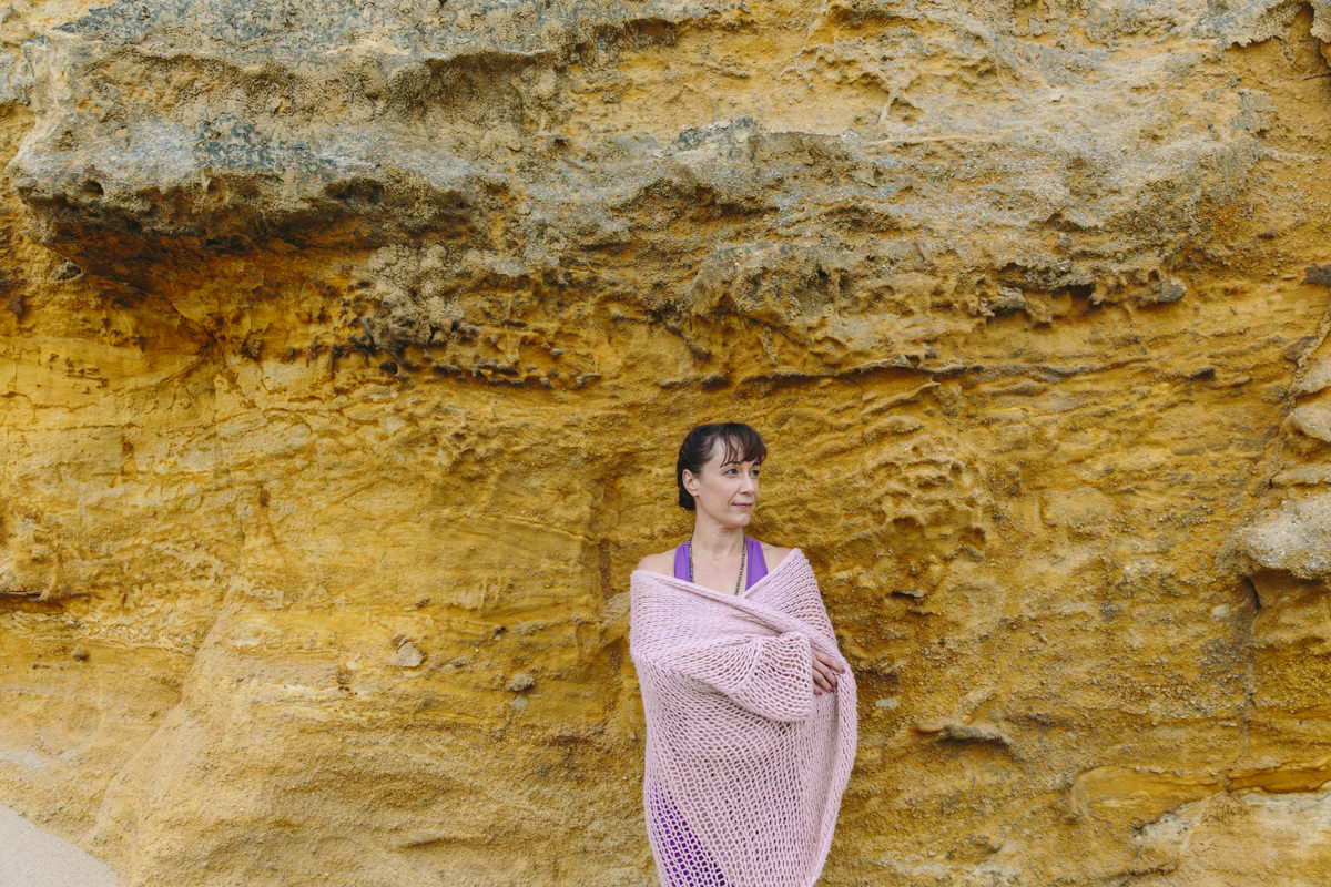 Portrait von Yogalehrerin Christine Mack vor einer gelben Steinwand an der Küste Portugals | Foto: Hanna Witte