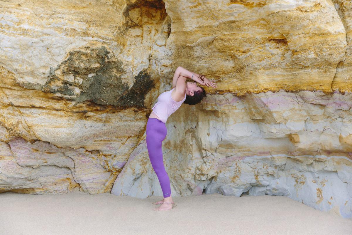Yoga Portrait von Wellness Coach Christine Mack vor einem gelben Felsen am Strand von Portugal | Foto: Hanna Witte