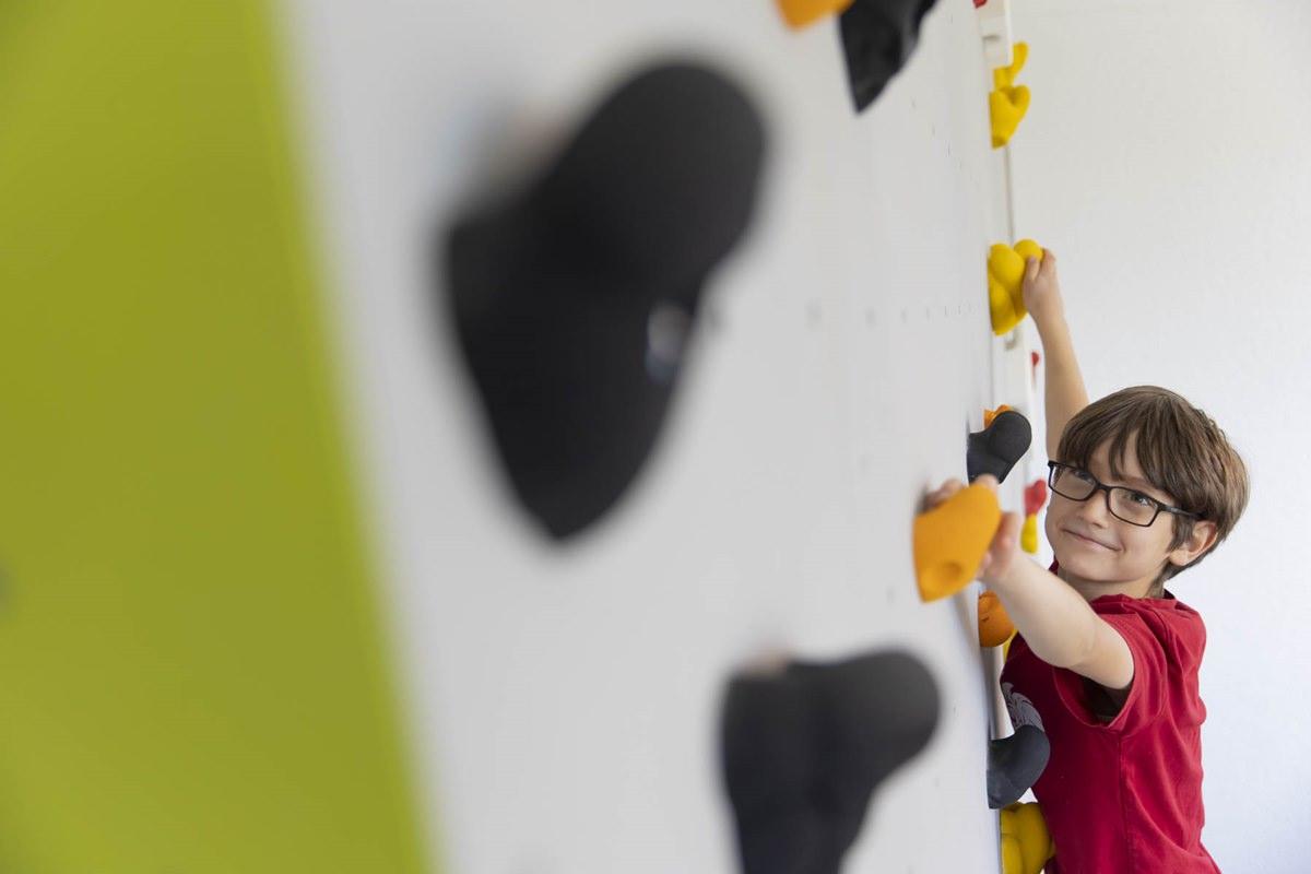 ein Junge klettert an einer Boulderwand im Familienhotel Ottonenhof | Foto: Hanna Witte