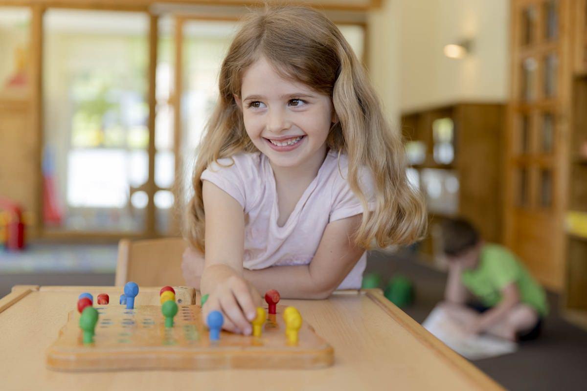 ein Mädchen spielt ein Brettspiel im Innenbereich des Familienhotels Ottonenhof | Foto: Hanna Witte