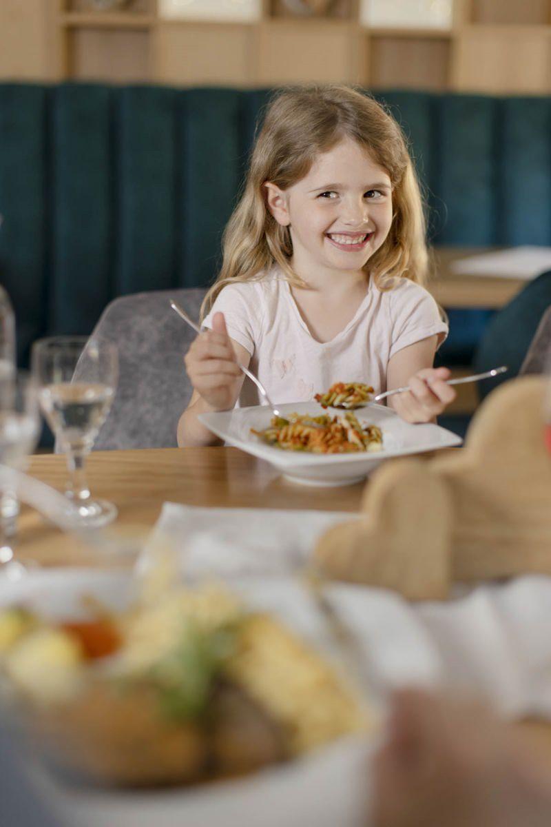 ein Mädchen isst Nudeln im Essensbereich des Familienhotel Ottonenhof | Foto: Hanna Witte