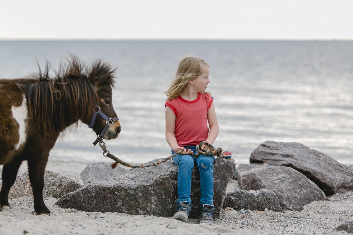 Foto von einem Kind am Strand mit einem Pony des Ferienhofs Bauer Martin | Foto: Hanna Witte