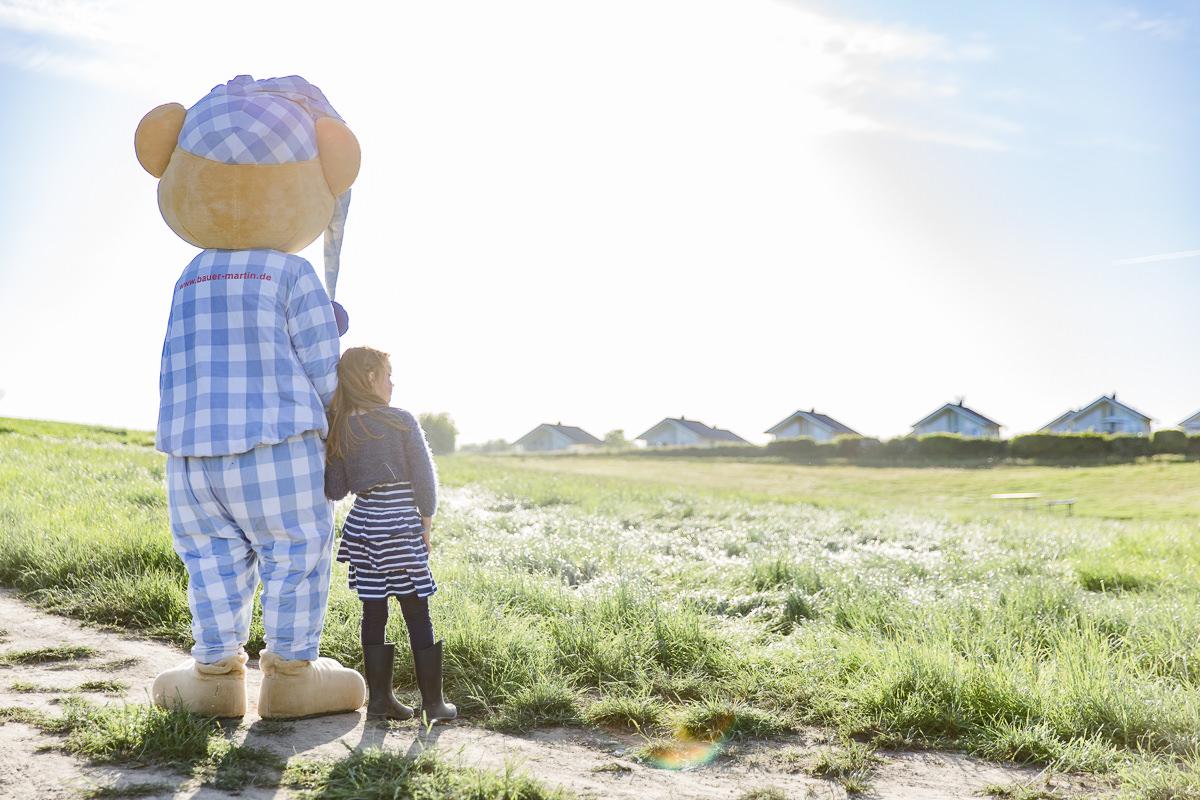 Foto von dem Maskottchen des Familienhotels Bauer Martin mit einem Kind in der Natur | Foto: Hanna Witte