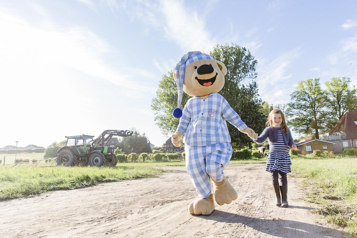 Foto vom Maskottchen des Familienhotels Bauer Martin beim Spaziergang mit einem Mädchen