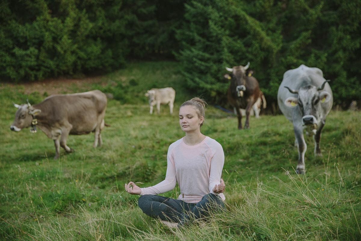 eine Frau beim Yoga zwischen Kühen auf einer Wiese im Allgäu | Foto: Hanna Witte