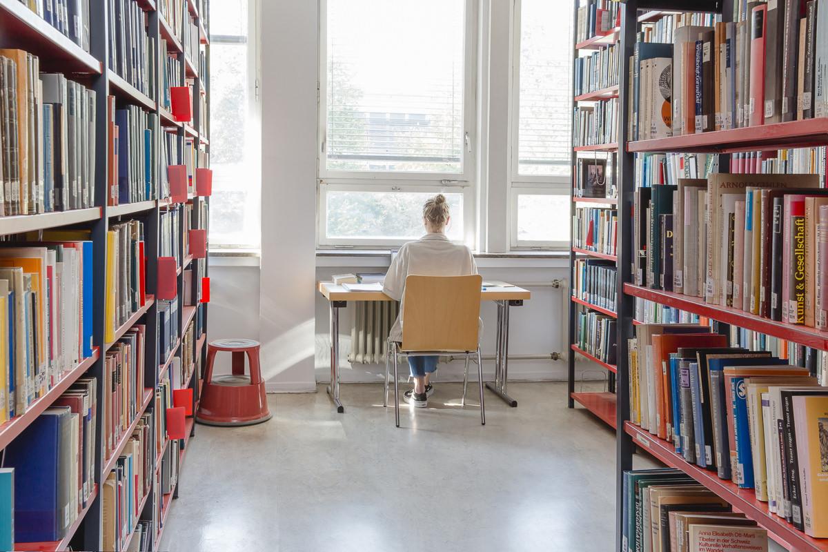 eine Soziologie Studentin der Uni Tübingen lernt an einem Schreibtisch in der Bibliothek | Foto: Hanna Witte