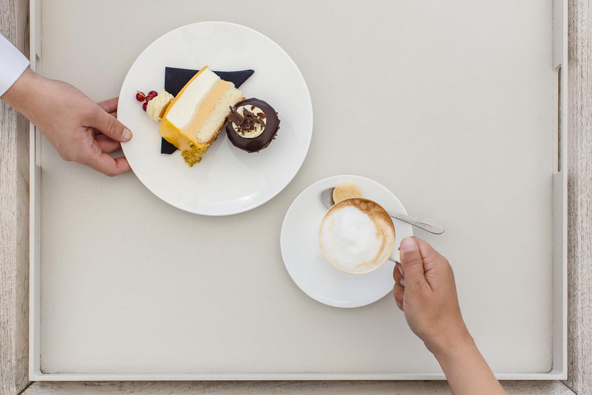 ein Gastronomiemitarbeiter serviert einem Gast Kaffe und Kuchen | Foto: Hanna Witte