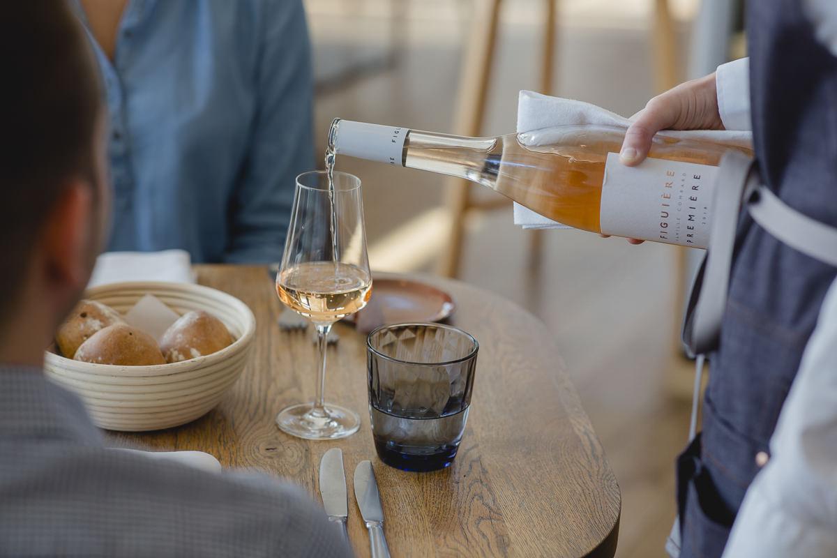 eine Mitarbeiterin des Lumi Restaurants im Wellnesshotel Seezeit Lodge gießt Wein ein | Foto: Hanna Witte
