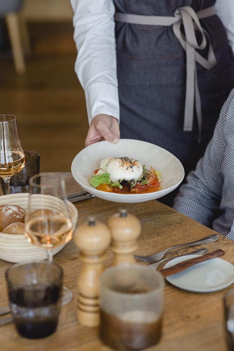 eine Mitarbeiterin des Lumi Restaurants im Wellnesshotel Seezeit Lodge serviert Essen | Foto: Hanna Witte