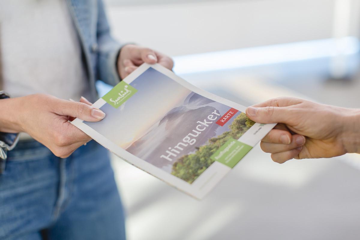 ein Mitarbeiter übergibt einem Besucher eine Info Broschüre über den Baumwipfelpfad Saarschleife | Foto: Hanna Witte