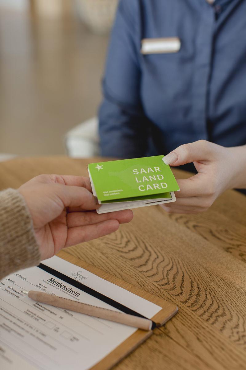 eine Service-Mitarbeiterin übergibt einem Gast die Saarland Card | Foto: Hanna Witte