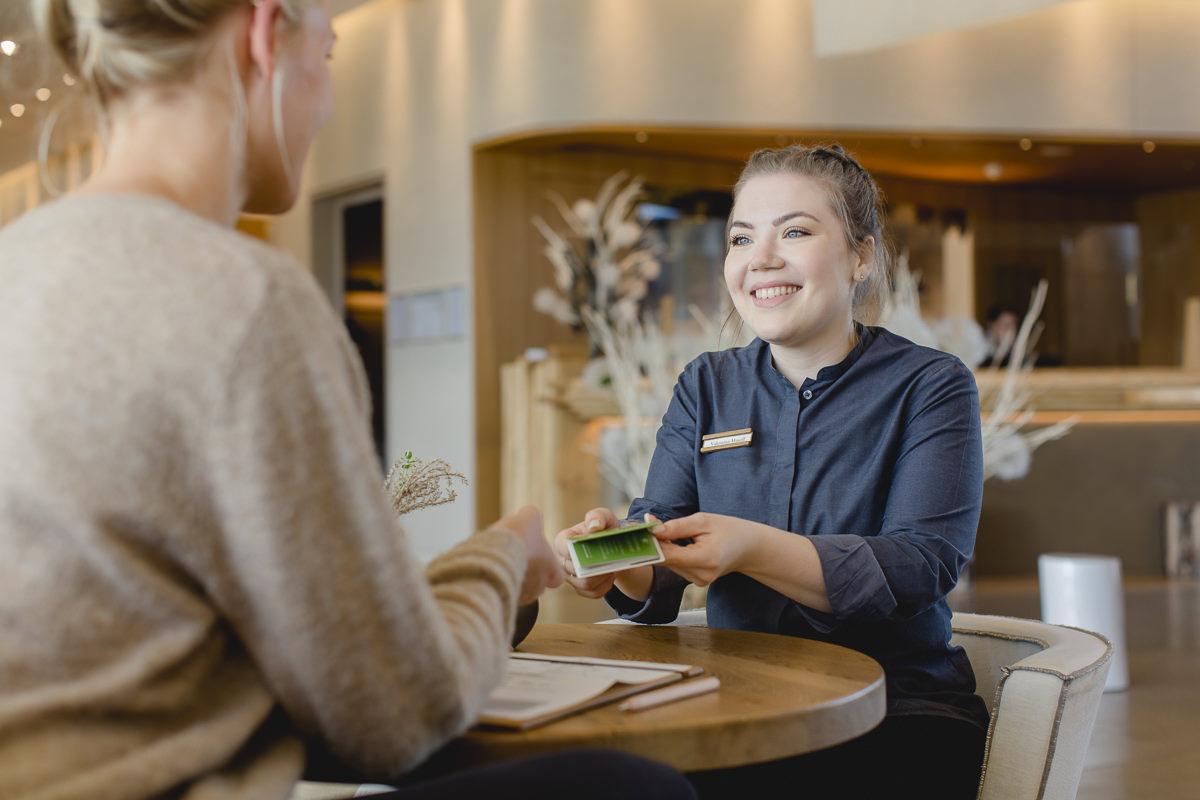 eine Service-Mitarbeiterin zeigt einem Gast die Saarland Card | Foto: Hanna Witte
